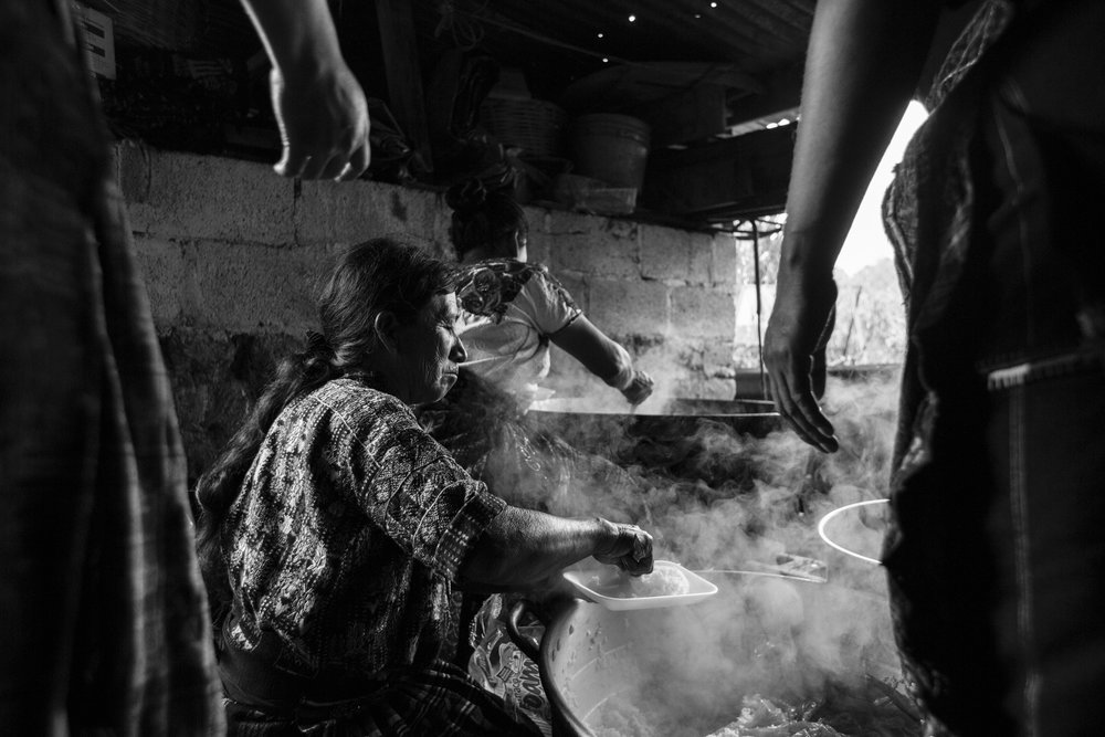 Women cook Pepián, a traditional Guatemalan dish, in a smoke filled area, for the guests of Jorge Mario's wedding in Sololá, Guatemala.