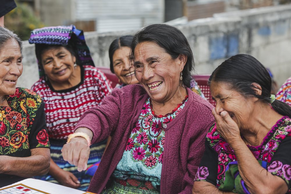 A group of women smile and laugh during a game of bingo at an elderly care  center in Patanatic, Guatemala, on January 10, 2019.
