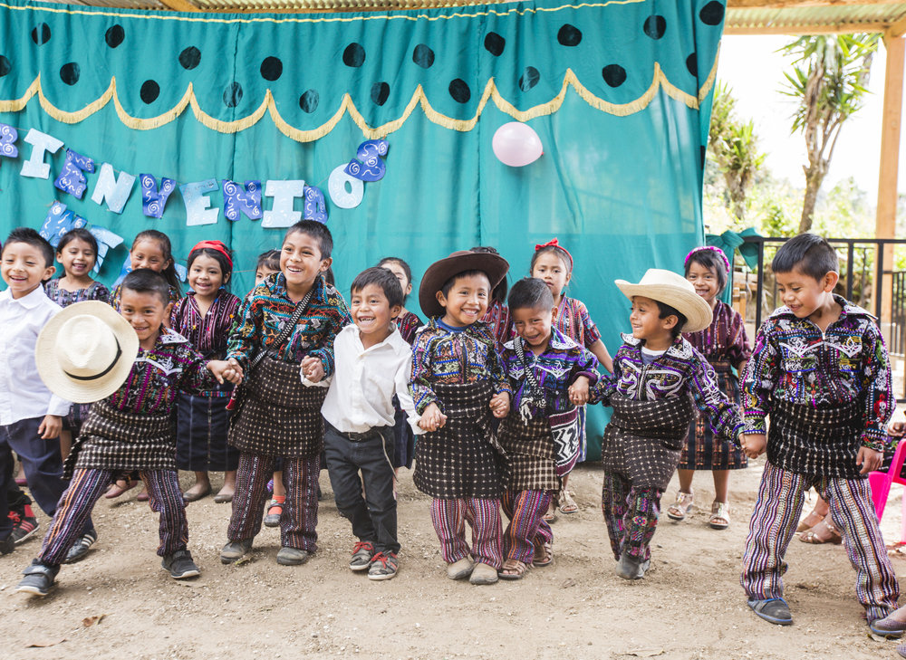 Children do a traditional Maya dance at their preschool in a small community, Peña Blanca, Guatemala, on November 23, 2018. These students are wearing traditional traje (clothing) which is an essential aspect of the Maya culture. Traje is unique for its storytelling function, as each color and stitch cultivate imperative meanings. Garments serve as an expression of both identity and geography.