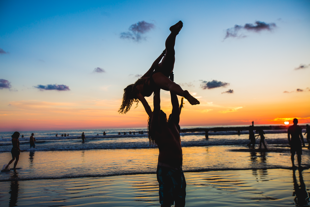 A couple does yoga on Uvita Beach in Costa Rica, during Envision Festival on March 2, 2019.
