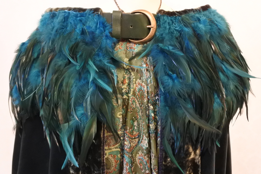 Buckle and feather detail on cape.