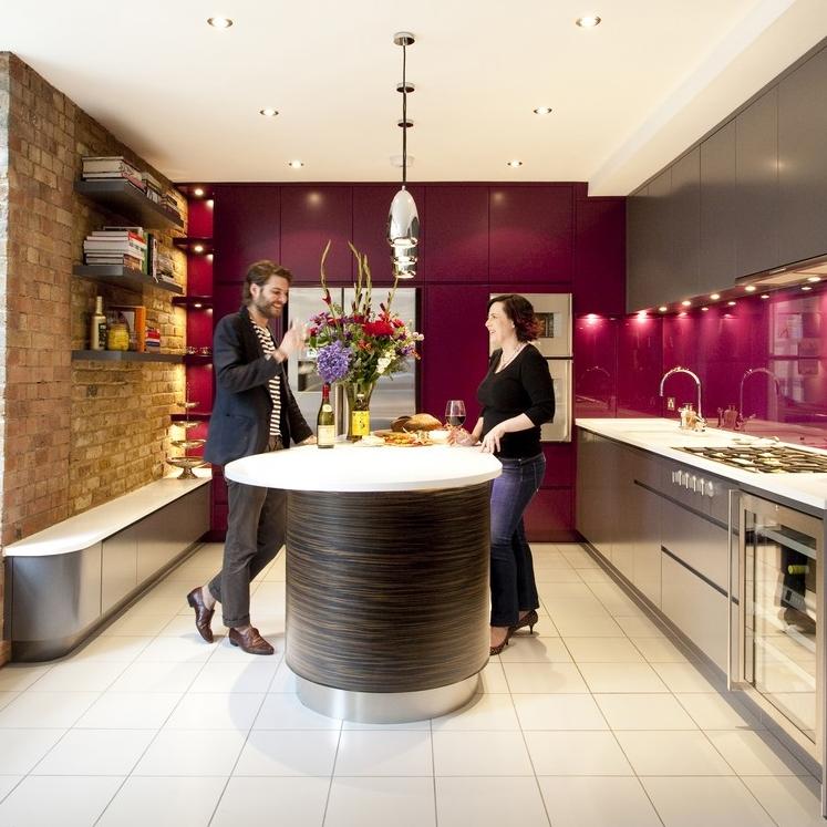 Modern Bespoke Kitchen.Wooden Island Cooking. Purple and Grey Lacquer. Purple Glass Splashback. Brick Wall. White tiles.