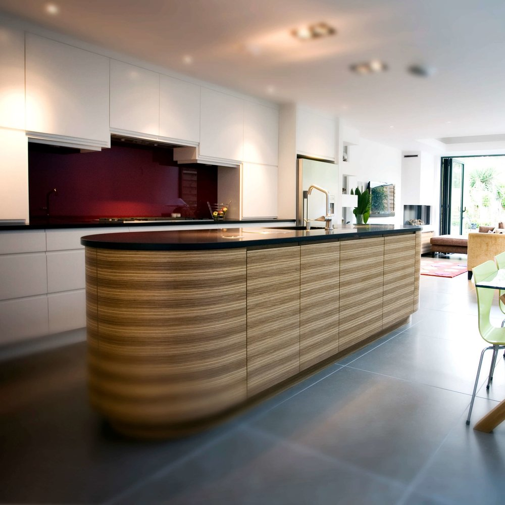 Modern Bespoke Kitchen. Open Plan. White Lacquer Cupboards. Zebrano Wooden Island. Oval Island. Red Glass Splash back.