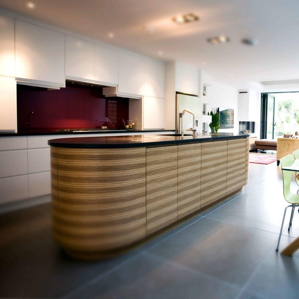 Modern Bespoke Kitchen. Open Plan. White Lacquer Cupboards. Zebrano Wooden Island. Red Glass Splash back.