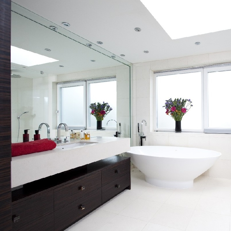 Elegant Bespoke Bathrooms. Ebony Bespoke Furniture. Full Walled Mirror. Full Mirror Frame. Floating Basin. Bright Bathroom. Marble. Freestanding Bath. Italian Shower. Limestone.