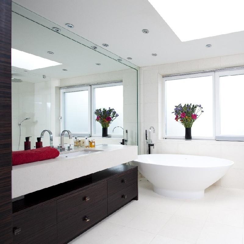 Elegant Bespoke Bathrooms. Ebony Bespoke Furniture. Full Walled Mirror. Full Mirror Frame. Floating Basin. Bright Bathroom. Marble. Freestanding Bath. Italian Shower. Limestone.
