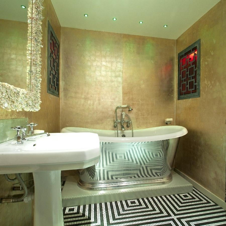 Luxury Interior Design. Bespoke Furniture. Highest Quality Finishes. Luxury Warehouse Design. David Carter Design. Bespoke Shiny Bathroom. Gold Painted Walls. Freestanding Bath. Mirror Bath. Black and White Tiles.