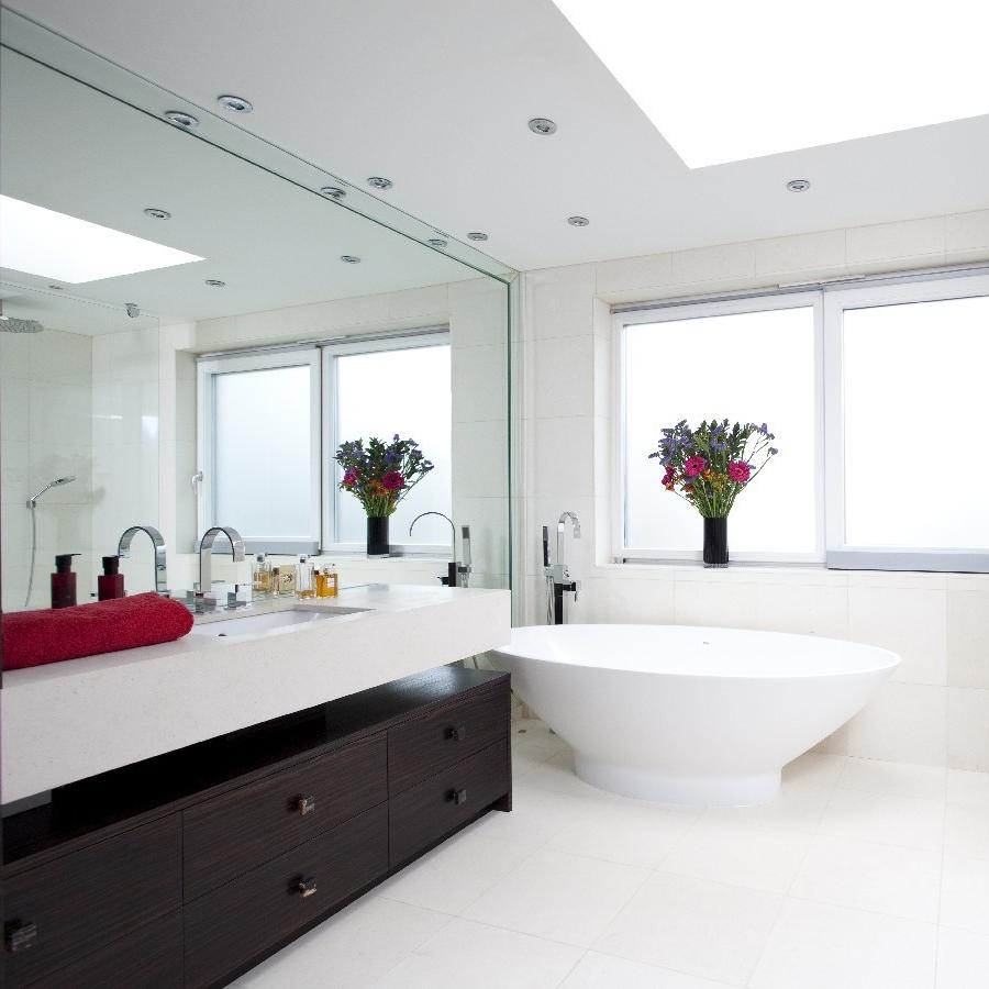 Luxury Bespoke Bathroom. Large Walled Mirror. Frame Mirror. Macassar Bespoke Cupboard. Freestanding Bath. Limestone Wall and Floor.