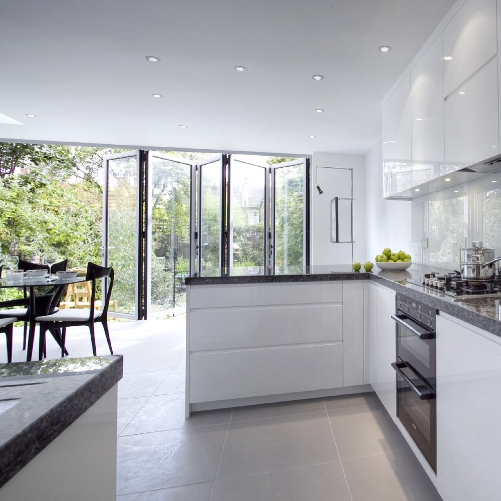 Modern/Contemporary Interior Design Kitchen. Bespoke Kitchen. Open Plan. White Lacquer. Blue Granite. Large sociable Kitchen. Light Grey Tiles. Glass Family Table. Black Veneer Chairs.