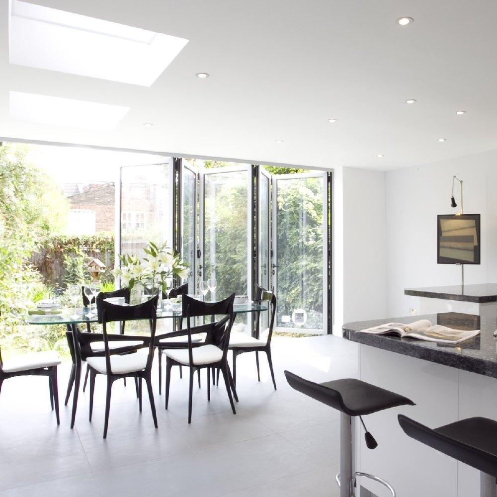 Modern/Contemporary Interior Design Kitchen. Bespoke Kitchen. Open Plan. White Lacquer. Blue Granite. Large sociable Kitchen. Light Grey Tiles. Glass Family Table. Black Veneer Chairs. Breakfast Bar.