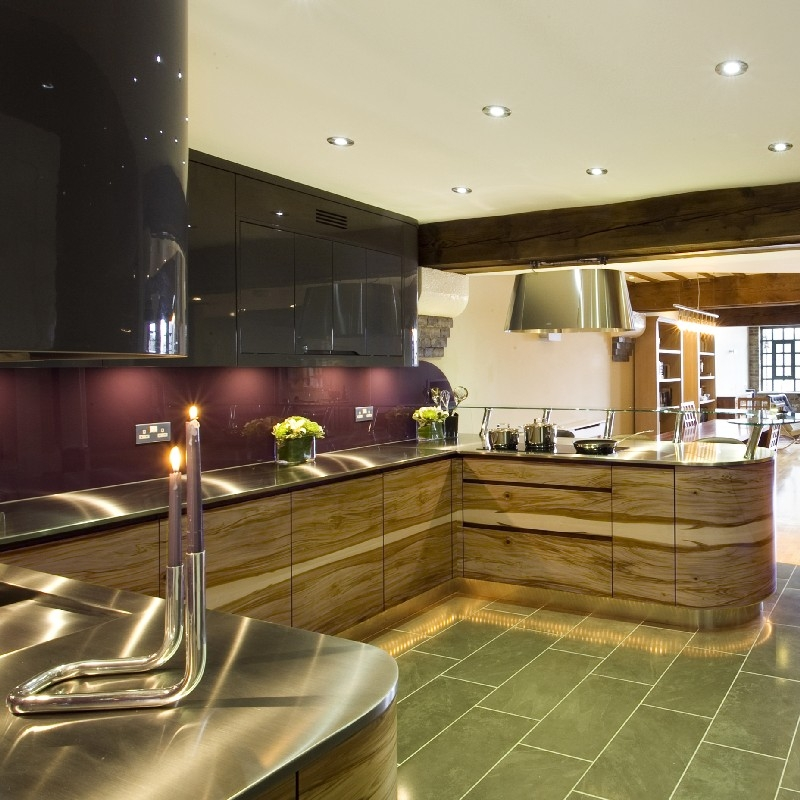 Modern Interior Design Kitchen. Bespoke Kitchen. Grey High-Gloss Lacquer. Mauve Splash Back. Stainless Steel Worktops. Curved Glass Breakfast Bar. Bespoke Wood Cupboard. Book-Matched Veneer. Grey Tiles.