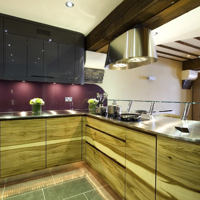 Modern Interior Design Kitchen. Bespoke Kitchen. Grey High-Gloss Lacquer. Mauve Splash Back. Stainless Steel Worktops. Curved Glass Breakfast Bar. Bespoke Wood Cupboard. Book-Matched Veneer. Grey Tiles. Stainless Steel Hood.