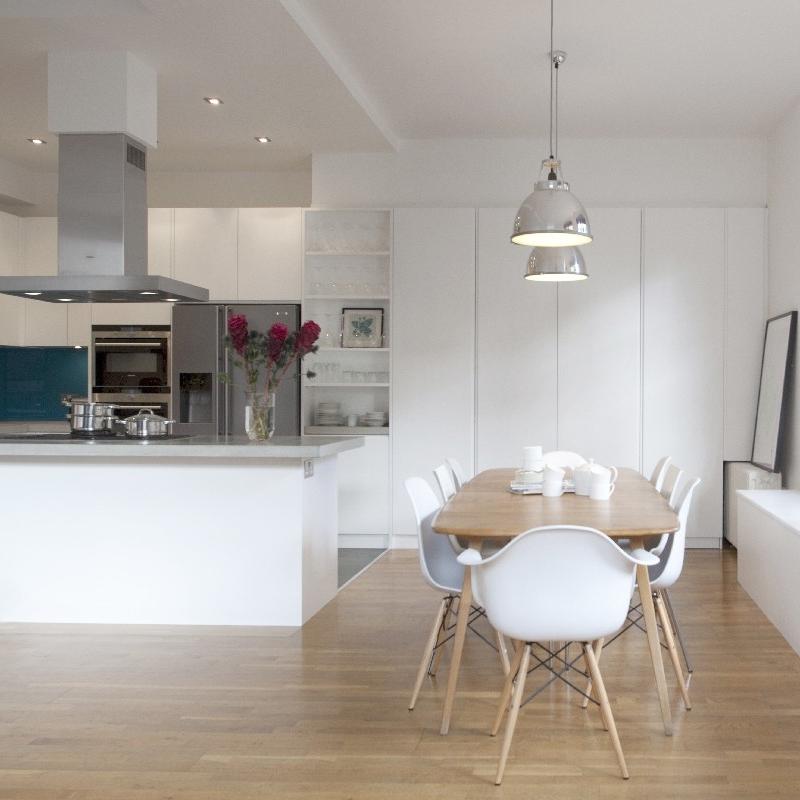 Bespoke Modern/Minimalist Kitchen Design.White Lacquer. Grey Concrete Worktops. Blue/Turquoise. Stale Floor.Open Plan Bespoke Kitchen. White Breakfast Bar. Large Cupboard. Family Wood Table.