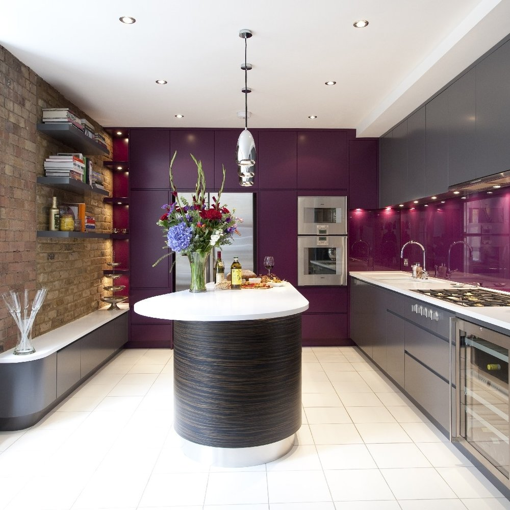 Modern Bespoke Kitchen. Macassar Wooden Island Cooking. Purple and Grey Lacquer. Purple Glass Splash Back. Brick Wall. White Tiles. Bespoke Furniture.