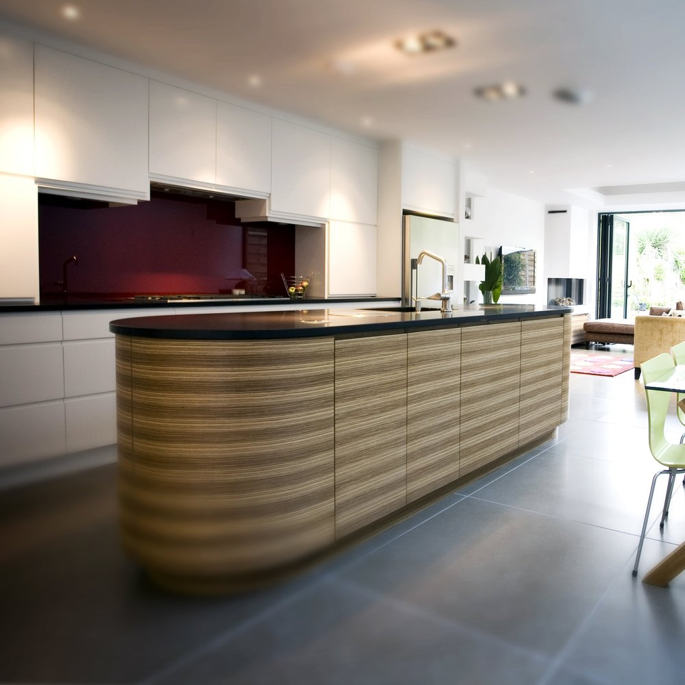 Modern Bespoke Kitchen. Open Plan. White Lacquer Cupboard. Bespoke Furniture. Zebrano Wooden Island. Red Glass Splash Back. Open Plan