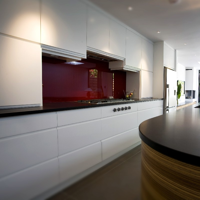 Modern Bespoke Kitchen. Open Plan. White Lacquer Cupboards. Zebrano Wooden Island. Red Glass Splash Back. Black Worktops.