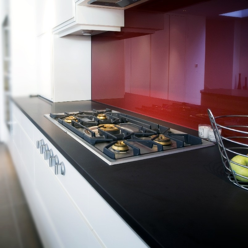 Modern Bespoke Kitchen. Open Plan. White Lacquer Cupboards. Red Glass Splash Back. Stainless Steel Gas Hob. Black Worktops.
