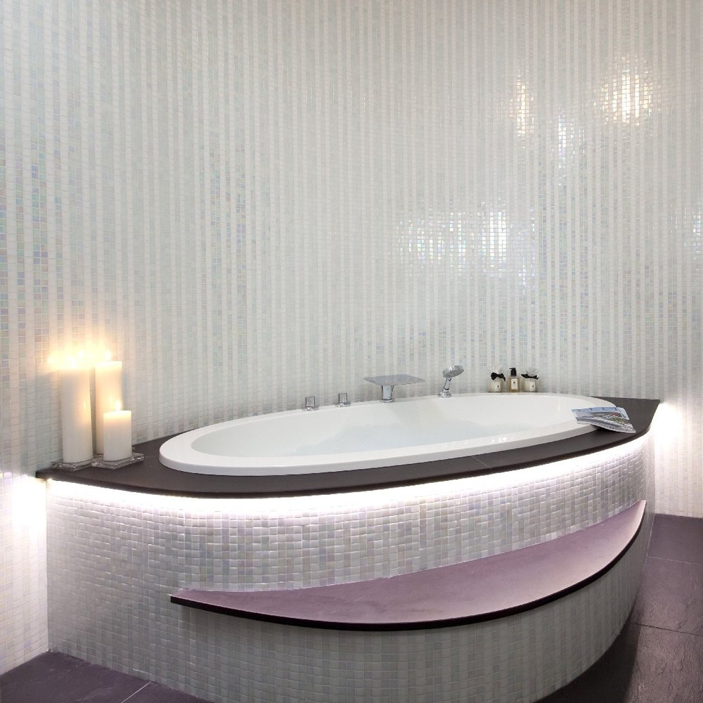 Luxury Glamorous Bespoke Bathroom. Incandescent White Tiles. Large Raised Bath. Light and bright Bathroom.