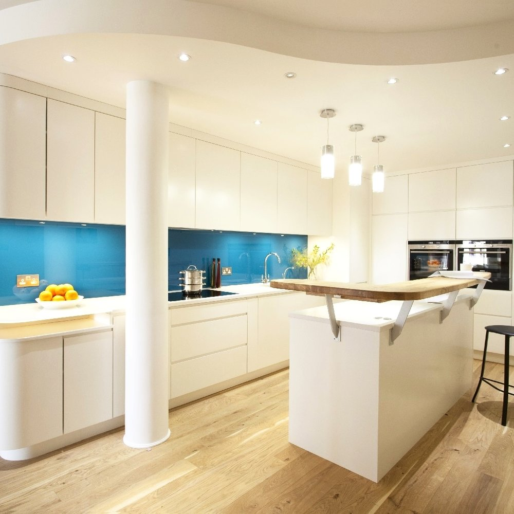 Luxury Interior Design. Bespoke Kitchen. Simple and Bright Kitchen. White Lacquer. Blue Glass Splash Back. Wooden Floor. Breakfast Bar Island.
