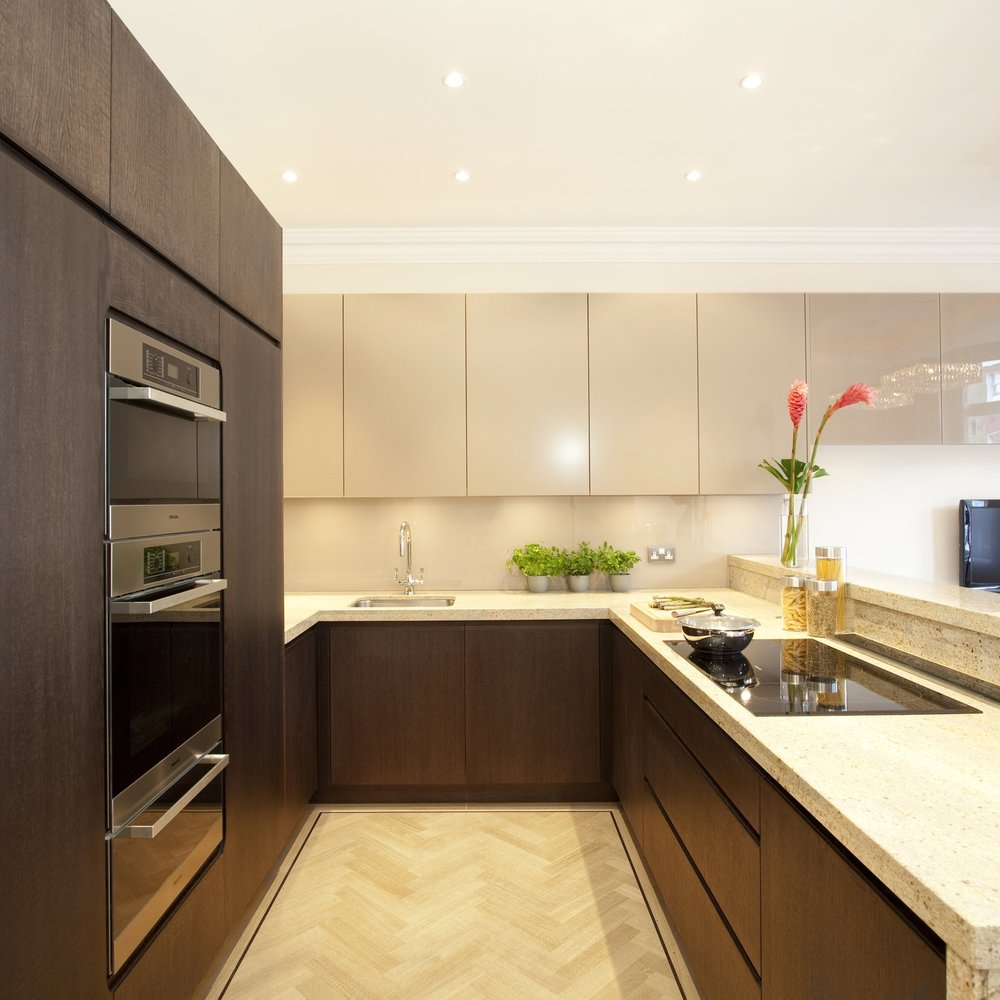 Modern/Contemporary Bespoke Kitchen. Beige Lacquer Cabinetry. Dark Wooden Furniture. Granite Worktops. Light Wooden Floor.