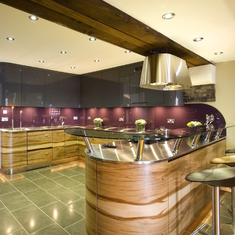 Luxury Contemporary Design Kitchen. Stainless Steel Worktops. Curved Glass Breakfast Bar. Bespoke Furniture. Book-Matched Veneer. Grey High-Gloss Lacquer Cabinetry. Mauve Glass Splash Back.