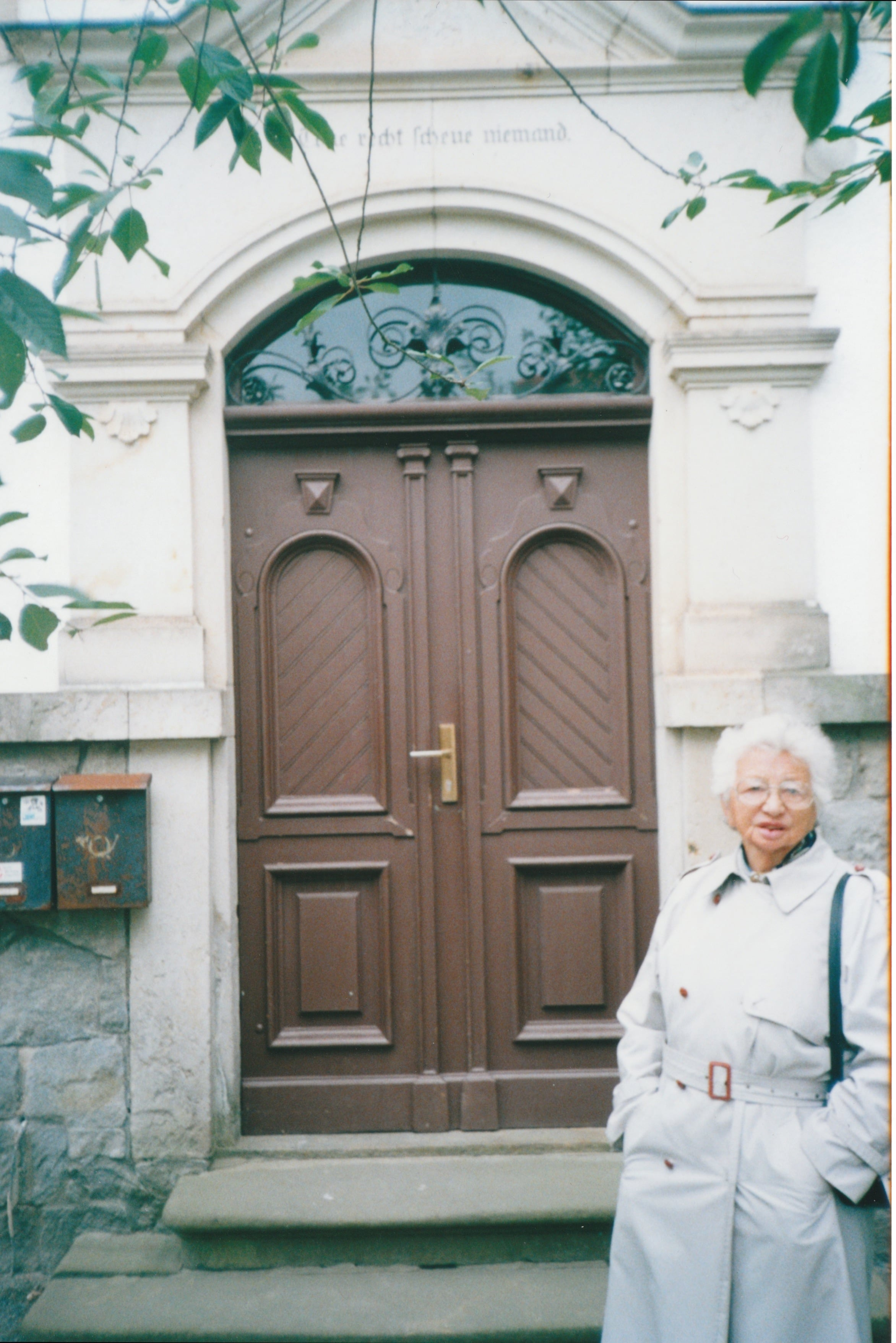 "Rike outside the doorway of her childhood home on a visit in 2000.  Above the doorway is the inscription, ""Do right and fear no-one""."