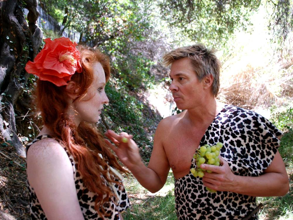 Molly Elizabeth Ring being fed a grape on set by co-star Kato Kaelin.
