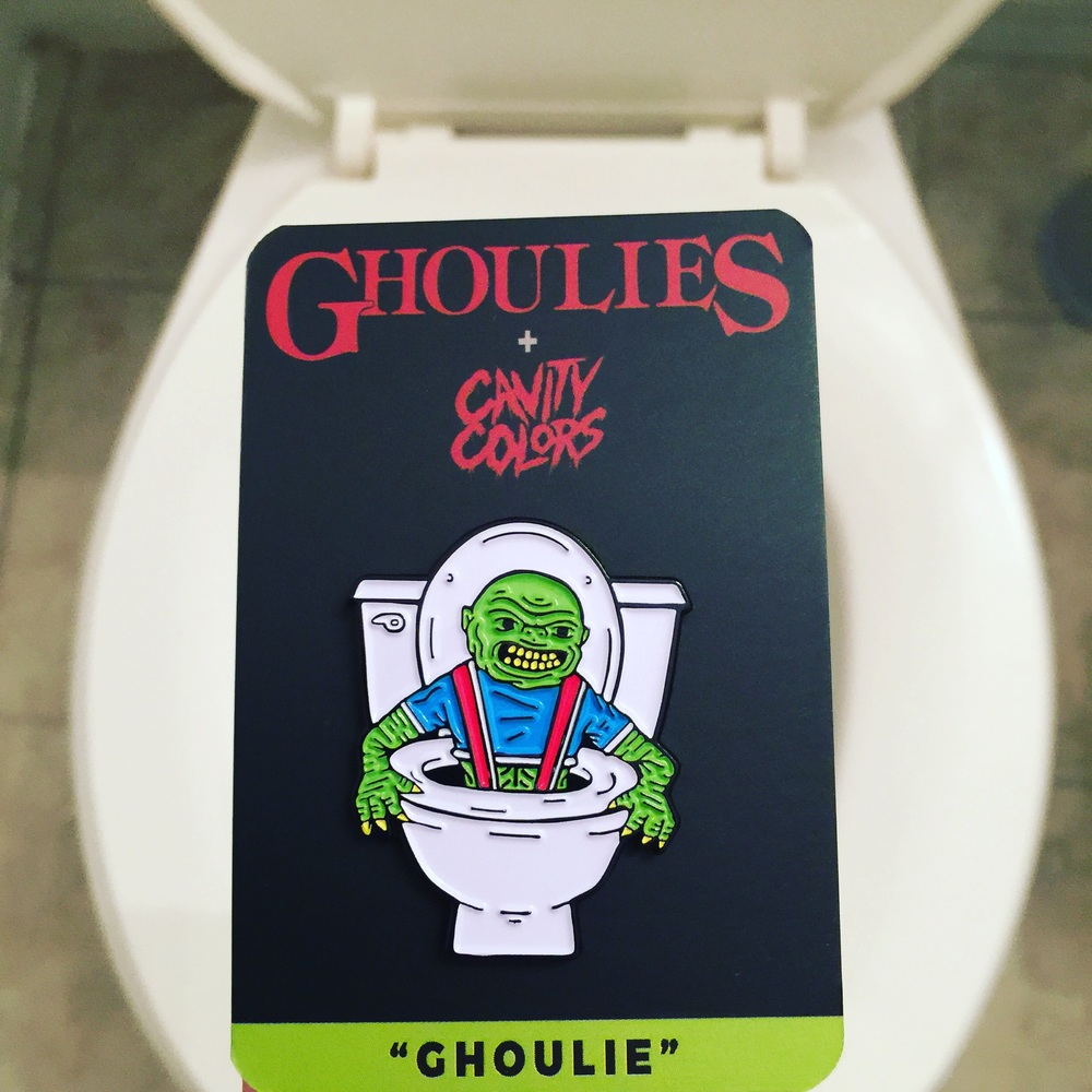 THEY'LL GET YOU IN THE END! We are proud to present our officially licensed GHOULIES merch! This one features a rendition of the classic VHS box art image, in ENAMEL PIN form!   LIMITED EDITION OF 300 ENAMEL PINS - NO RE-STOCKS ON THIS PIN, EVER!  - 1.5 inches tall - Soft Enamel pin with a shiny black finish - Double rubber clutch on the back for secure attachment - Cavitycolors logo stamp on the back - Pin comes attached to a custom backing card ART BY: Bruce Parker & Aaron Crawford