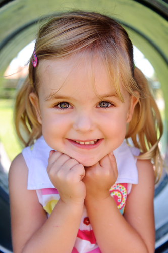 little girl in tunnel smiling