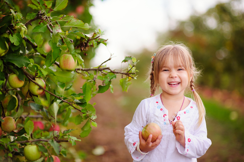 girl in a grove with a piece of fruit smiling