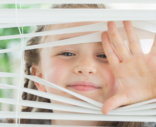 Little girl looking through blinds