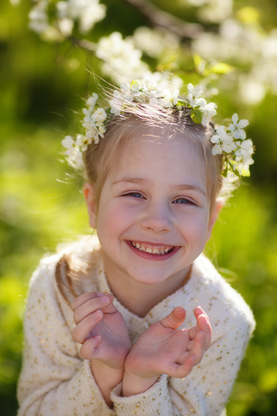 little girl with flowers in her hair smiling