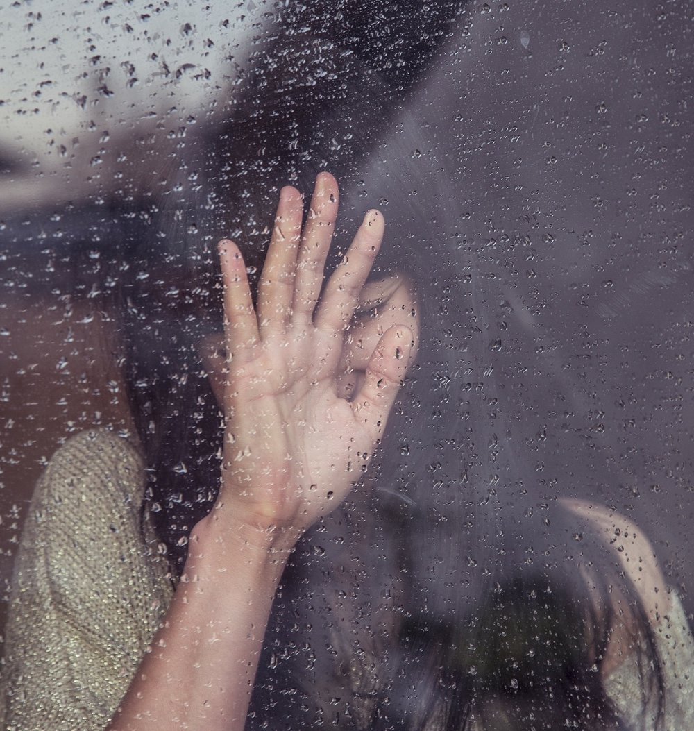 woman with hand to window that has raindrops on it