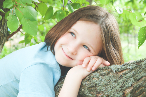 girl contently laying on a tree limb
