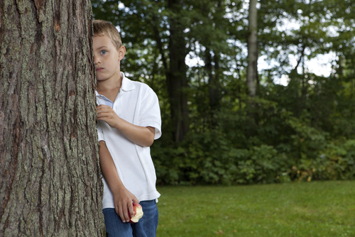 boy hiding behind a tree