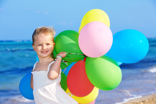 little girl at the beach with several different colored balloons