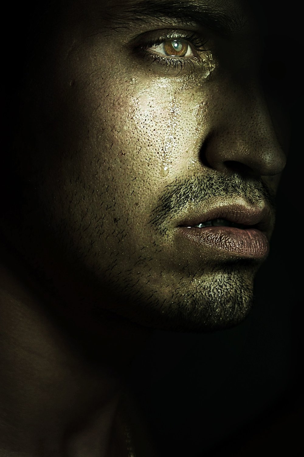 closeup of sad man with tear coming down his cheek