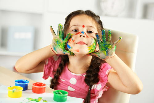 Little girl finger painting in play therapy