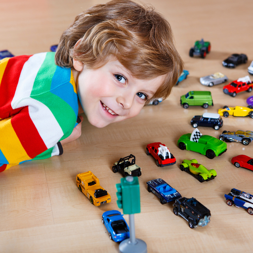 Little boy smiling with toy cars in play therapy