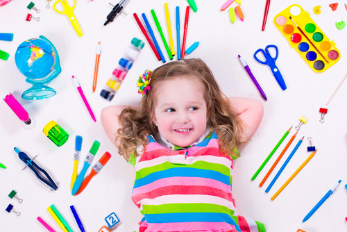 girl surrounded by paint brushes, paints, and scissors