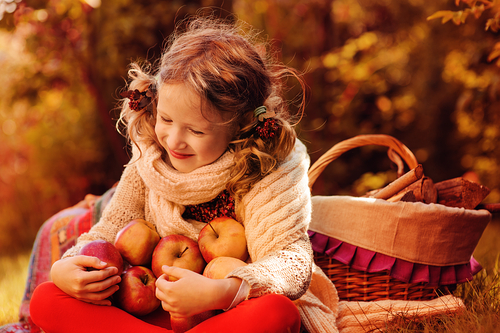 little girl gathering apples