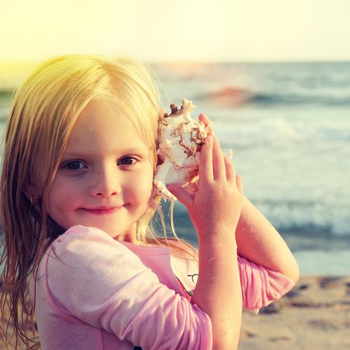 Child listening to sea shell