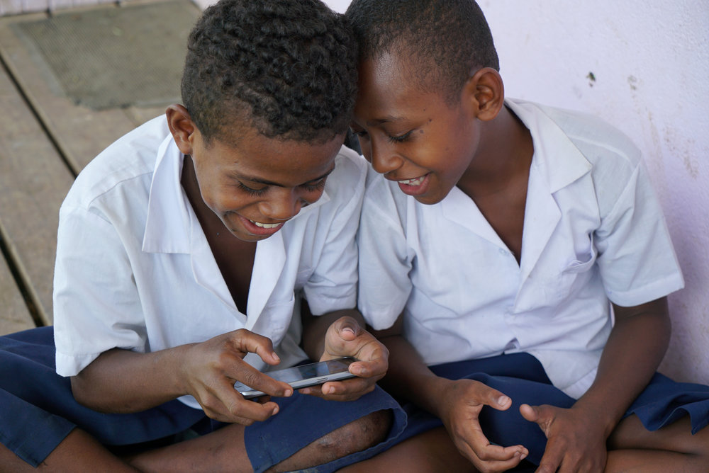 Students from Waiqanake Primary School in Fiji playing the BTS mobile game