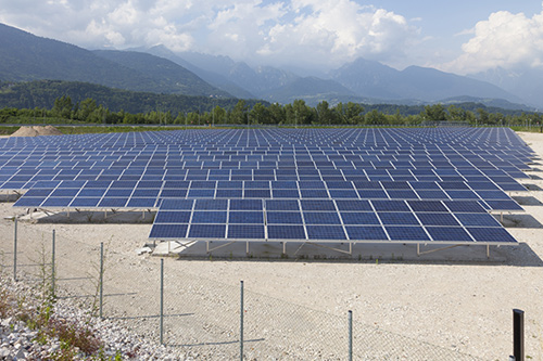 Dirt lot with rows of solar panels and mountains in the background