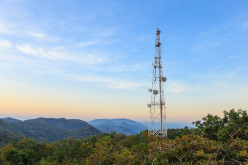 energy tower with blue sky and mountains and forest in background during summer