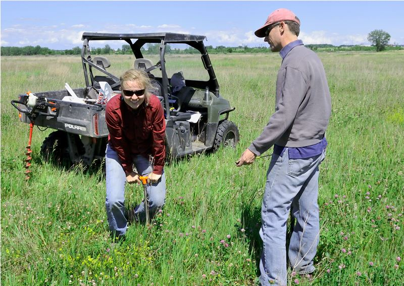 Former TWI restoration ecologist Iza Redlinski and GIS analyst Jim Monchak measure the depth to bedrock before installing a groundwater well at Lobelia Meadows.