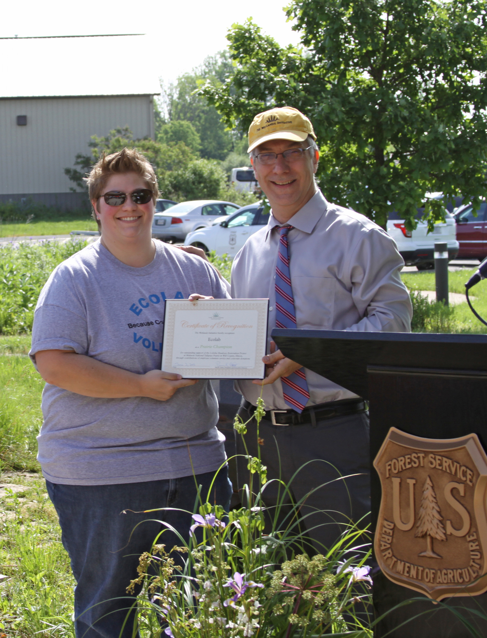 Kate McNichols of Ecolab receives a certificate of recognition from TWI Executive Director Paul Botts.