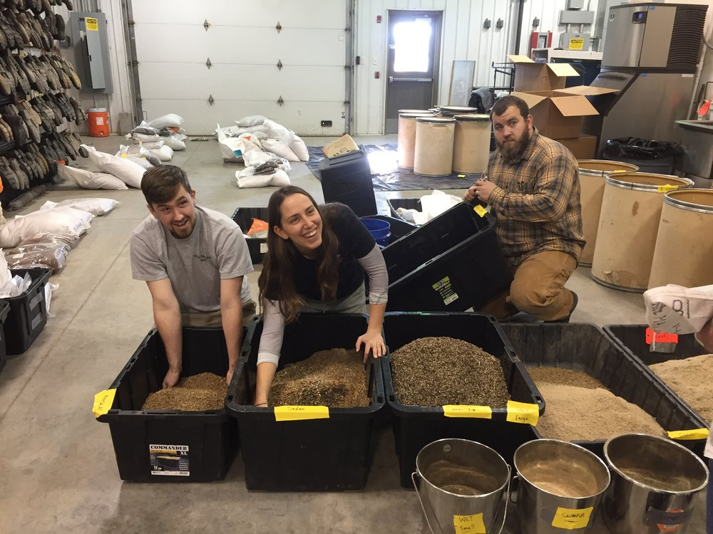 TWI field restoration crew members mix seed by hand in Midewin's horticulture building. Photo by Phoebe Thatcher/TWI.
