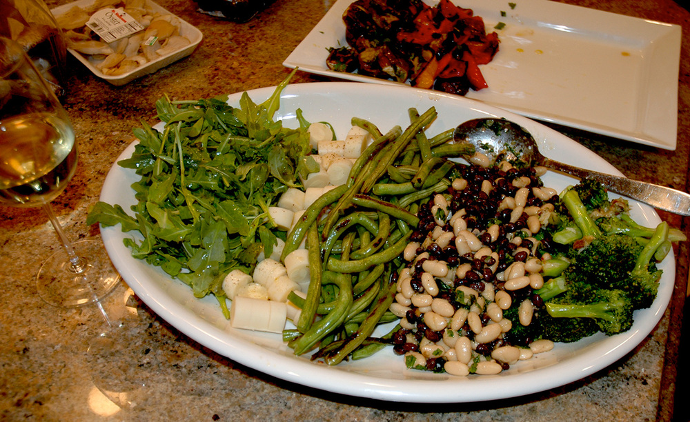 Greens and Whites platter is made up of arugula simply dressed with lemon juice, salt and olive oil, next to hearts of palm, sautéd string beans, 2 bean salad and roasted broccoli.