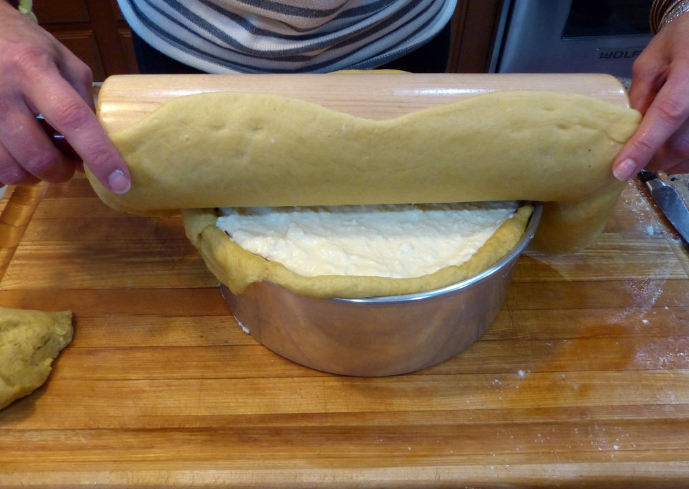 Since the dough is quite pliable, it's much easier if you roll it onto the rolling pin and they roll it onto the top.